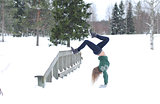 Girl performs gymnastic exercise in the fresh air in winter