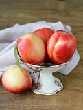 ripe fresh pink peaches in vase on a wooden table