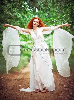 Beautiful redhead woman wearing white dress in a garden