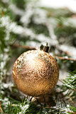 Gold Christmas ornament on leaves