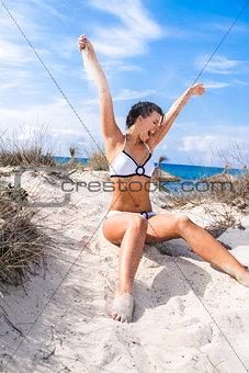 Beautiful woman sitting on golden beach sand