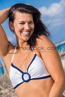 Beautiful woman sitting on golden beach sand