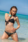 Female model wearing black bikini in the water