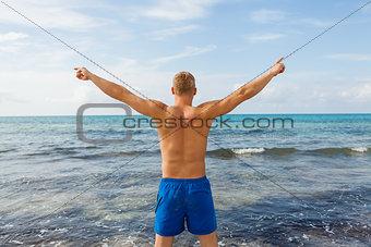 Man in blue swim shorts in the beach