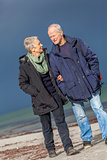 happy elderly senior couple walking on beach