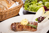 Grilled beef steak topped with butter and rosemary