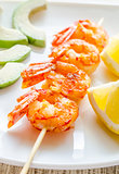 Shrimps skewers with avocado and lemon slices