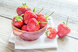 Fresh strawberries in the bowl on the wooden table
