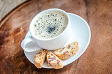 A cup of coffee with biscotti