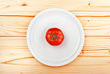 Fresh ripe tomato served on white plate on wooden kitchen table