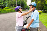happy grandmother help grandfather to wear a helmet