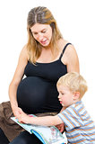 Beautiful pregnant happy mother with child boy reading book isol