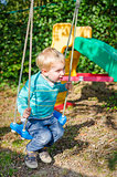 Cute little blond boy swinging on swings outdoor playground