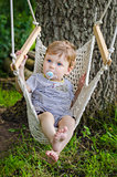 Little cute baby boy riding on hammock swing at park