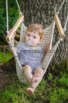 Little cute baby boy riding on hammock swing at park