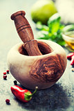 Wooden Mortar and Pestle and chilli peppers, herbs and spices