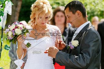 beautiful young wedding couple exchange wedding rings