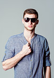 Studio fashion shot: handsome young man wearing shirt and sunglasses