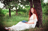 Lovely redhead woman sitting under tree and reading a book