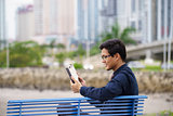 Portrait of asian office worker with ipad on bench