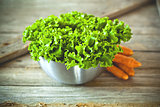 lettuce salad in metal bowl and carrots