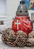 Red candle and pine cones on a marble grave in Brasov