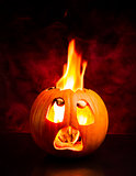 Scared face of Halloween pumpkin with flames and red smoke in the background.