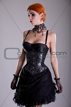 Pretty redhead young woman in silver corset and black skirt