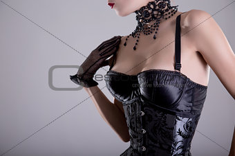 Close-up shot of elegant young woman in silver corset