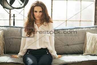 Portrait of young woman sitting on couch in loft apartment