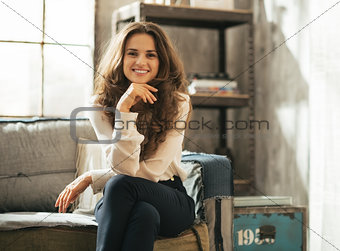 Happy young woman sitting in loft apartment