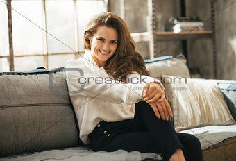Portrait of happy young woman sitting in loft apartment