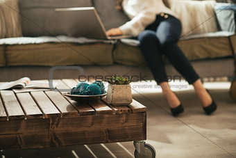 Closeup on coffee table and young woman using laptop in backgrou