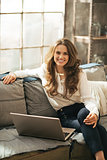 Portrait of happy young woman with laptop in loft apartment
