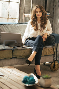 Portrait of young woman with laptop in loft apartment