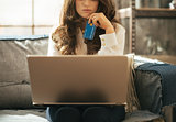 Closeup on thoughtful young woman with credit card using laptop
