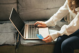 Closeup on young woman with credit card using laptop in loft apa