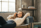 Happy young woman laying on sofa and talking cell phone in loft