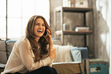 Portrait of smiling young woman talking cell phone in loft apart