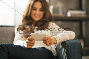 Closeup on happy young woman writing sms in loft apartment