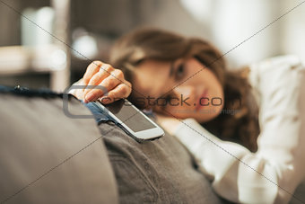 Closeup on thoughtful young woman with cell phone sitting on cou