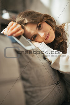 Concerned young woman with cell phone sitting on couch