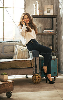 Smiling young woman talking cell phone in loft apartment