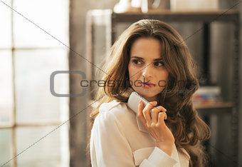 Portrait of thoughtful young woman with cell phone in loft apart