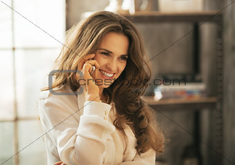 Portrait of happy young woman talking cell phone in loft apartme