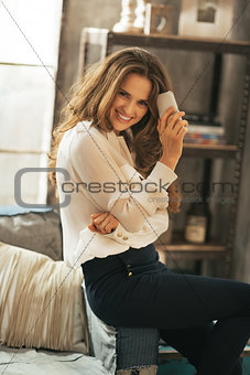 Portrait of happy young woman with cell phone in loft apartment