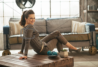 Happy young woman sitting on coffee table in loft apartment