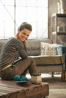Smiling young woman sitting on coffee table in loft apartment