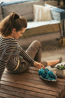 Thoughtful young woman sitting on coffee table in loft apartment
