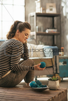 Young woman sitting on coffee table in loft apartment